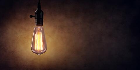 Vintage Hanging Light Bulb Over Dark Wall