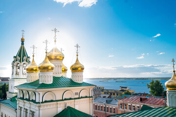 Golden domes with crosses on Orthodox Church of St John the Baptist, on the background of blue sky and Volga river. Russia, Nizhny Novgorod