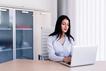 Attractive woman sitting in office and typing on her laptop