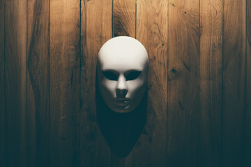 Mask hanging on the wooden wall in spooky light Mystical and horrible look.
