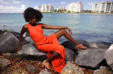 Stock image of a young black woman posing in the park in an orange jumpsuit