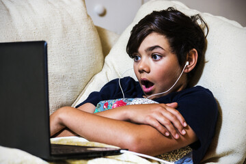 Adolescent boy with an expression of astonishment or shock using a laptop
