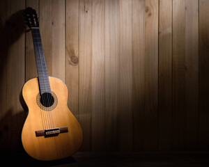 Acoustic guitar on wood background with copy space.