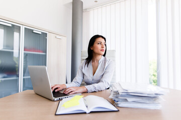 Attractive businesswoman looking trhougt window of her office while shes typing on laptop