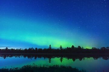 Silhouetted line of trees, vibrant Northern Lights and bright stars reflected in calm water
