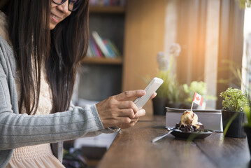 Beautiful woman wearing glasses take picture phone of cake (on wooden table) in cafe.Technology,food and drink concept.Bible and pot of tree on wooden table.