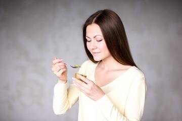 Beautiful young girl holding kiwi. Healthy food.