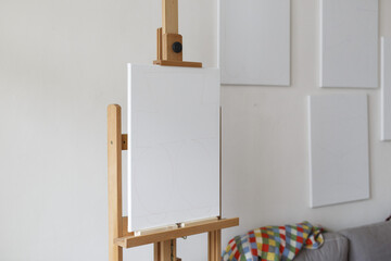 an empty canvas on an easel with multiple empty canvasses on the wall behind