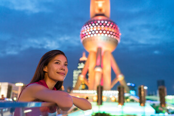 Shanghai city urban travel Asian woman tourist. Multiracial girl relaxing enjoying looking at city lights at night in Pudong, Shanghai, China with chinese landmark. Multicultural young professional.