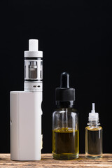 Electronic cigarette and aromas in bottles on a black background