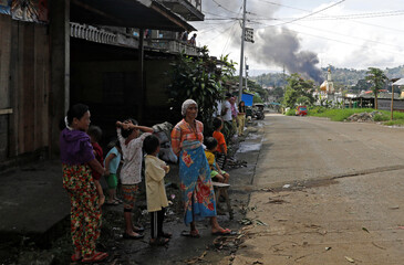 People stand on a roadside as billowing smoke is seen at the site of fighting between government soldiers and Maute group in Marawi City