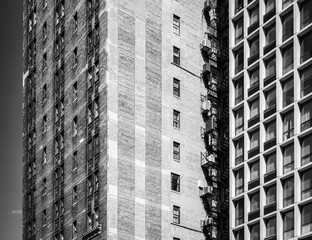 Black and white photo, view of block of flats. Apartment building made of bricks in Chicago downtown
