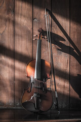vintage violin on wood background, dark tone