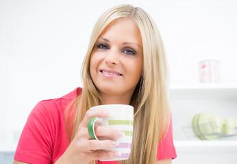 Junge Hausfrau bei einer Tasse Kaffee