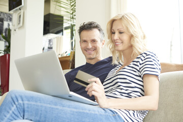 They like to shop online. Shot of a smiling middle aged couple sitting on couch and using credit card and laptop while shopping online.