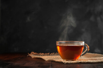 Photo sur Plexiglas The A Cup of freshly brewed black tea,escaping steam,warm soft light, darker background.