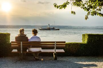 Senioren Paar auf Bank am See im Gegenlicht