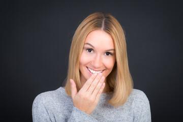 Hübsche junge Frau lächelt mit Hand am Mund