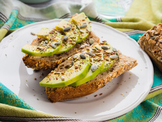 Avocado cereal sandwich for healthy snack with seeds on green napkin