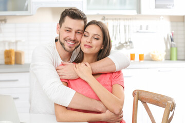 Young couple embracing at kitchen