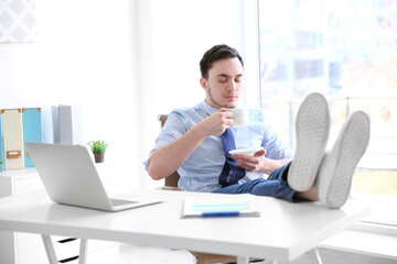 Young businessman relaxing at workplace with cup of coffee
