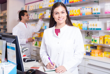 pharmaceutists at reception of drugstore ready to help