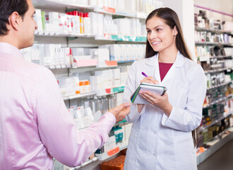 Pharmacist and consulting man in pharmacy
