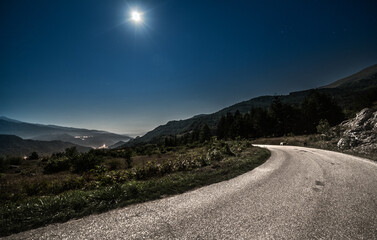 mountain road in the night with full moon in background.