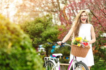 Young smiling girl standing near bicycle with basket of flowers in park