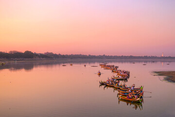 Traditional burmese boats on Taungthaman Lake at sunset, in Amarapura, Mandalay, Myanmar