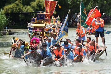 Participants take part in a dragon boat race to celebrate Dragon Boat festival at a wetland park in Hangzhou