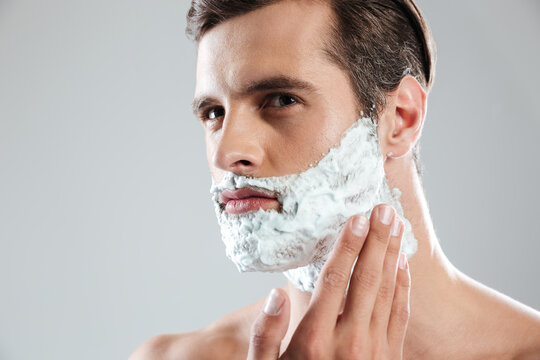 Concentrated man standing isolated with shaving foam on face