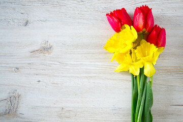 daffodils and tulips on white wooden surface