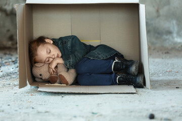 Poor little girl sleeping in cardboard box on street
