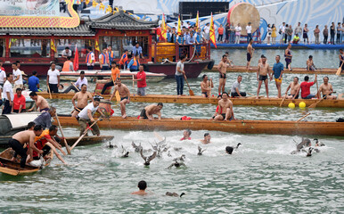 Participants of a dragon boat race join others in catching ducks after the race to celebrate Dragon Boat festival in Tongren, Guizhou
