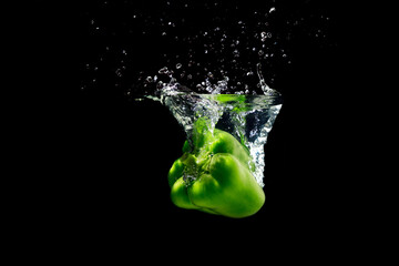 Green peppers splashing water on black background