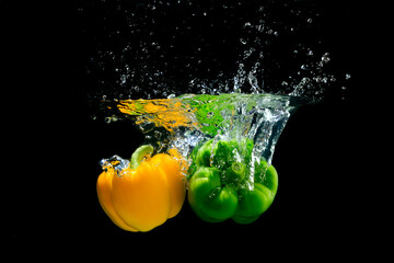 Yellow and green peppers splashing water on black background