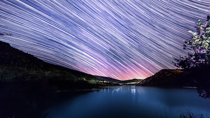 star trails over mountain lake