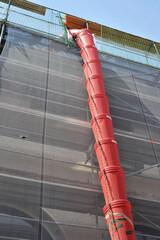 Teleskop-Bauschuttrutsche am Gerüst für die Renovierung der Fassade eines Verkaufsgebäudes mit Sicherheitsnetz