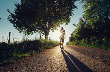 Traveler man silhouette on sunset road