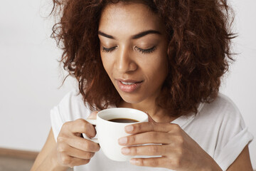 Close up of african girl holding cup smelling coffee with closed eyes.