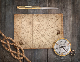 Fototapete - Old compass, rope, divider and vintage map on the wood desk.