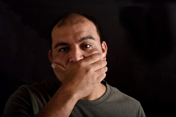 Man covering his mouth on black background
