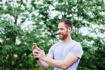 Casual guy in a park taking a photo