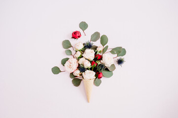 Waffle cone with red, beige roses and eucalyptus bouquet on pale pastel pink background. Flat lay, top view