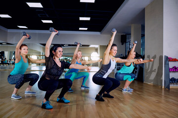 A group of sports girls doing sit-ups with dumbbells in the gym.