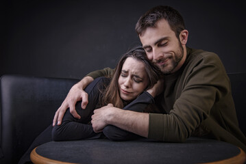 Young man comforting his girlfriend, hugging her and keeping her from harm, woman is crying and feeling sad Wall mural