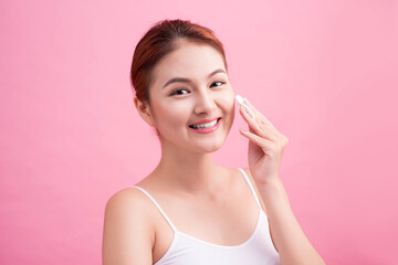 Healthy fresh asian girl removing makeup from her face with cotton pad.