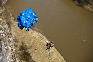 Basejumper jumping down from a cliff. Jump in the river canyon with a parachute.