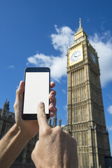 Hand touching screen of blank mobile phone in front of Big Ben and Westminster Palace in London under bright blue skies